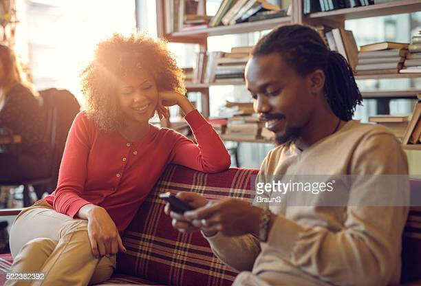 Happy African American woman looking at her boyfriend using phone.
