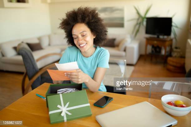 happy african american woman opening a present - receiving stock pictures, royalty-free photos & images