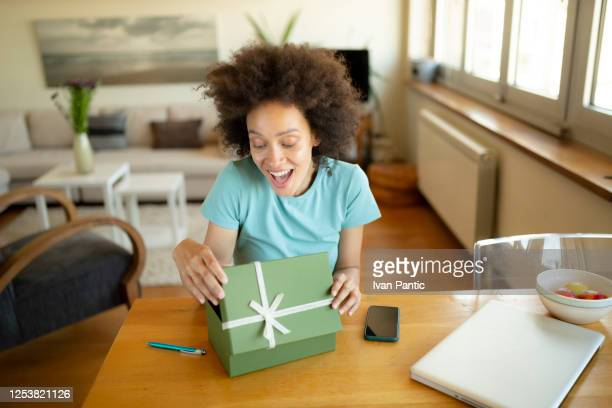happy african american woman opening a present - politics and government stock pictures, royalty-free photos & images