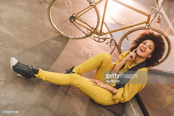 Heureuse femme afro-américaine, assis sur le sol et rire.