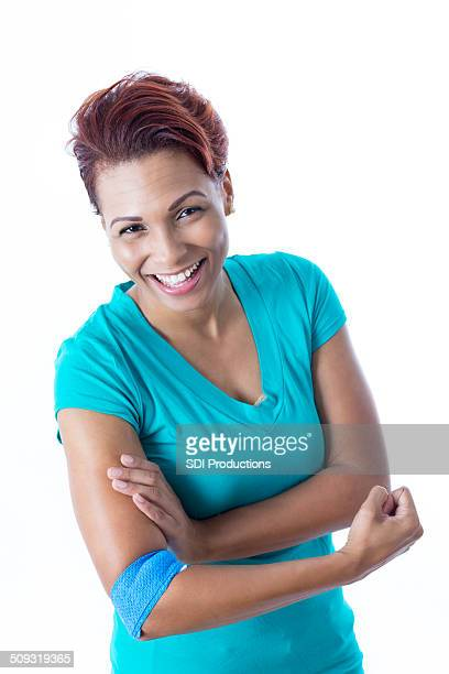 Happy African American woman with bandage after donating blood