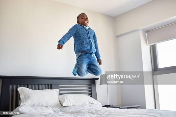 heureux garçon africain, s'amusant à la chambre le matin - pantalon noir photos et images de collection