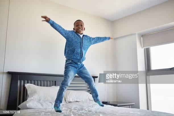 heureux garçon africain, sauter dans son lit le matin - pantalon noir photos et images de collection