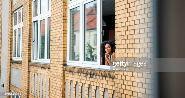 happy african business woman standing at window and admiring the view - looking at view stock pictures, royalty-free photos & images