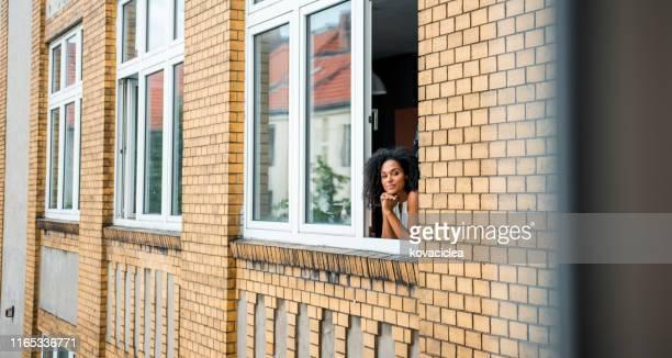 mulher de negócio africana feliz que está no indicador e que admira a vista - janela - fotografias e filmes do acervo
