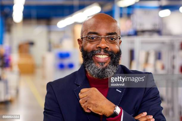Happy african businessman standing in factory