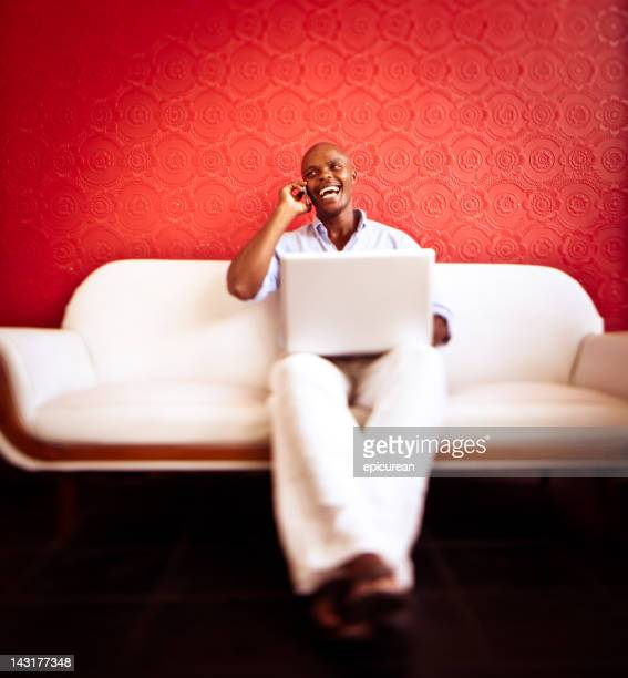 Happy African Businessman working on laptop and laughing