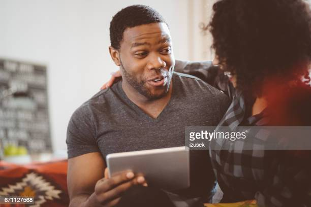 happy african couple at home with digital tablet - izusek stock pictures, royalty-free photos & images