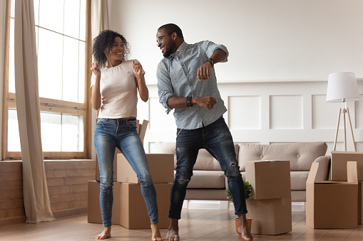 Happy african couple dancing laughing in living room with boxes 1158481670