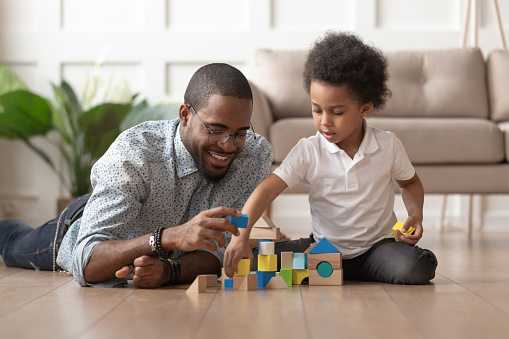 Happy african dad and child son building constructor from blocks 1158481694