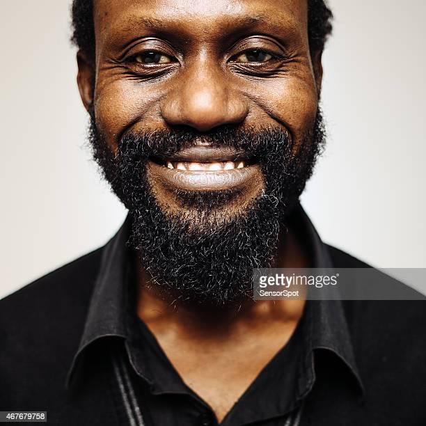 Heureux milieu âge homme portrait d'Afrique avec barbe souriant.