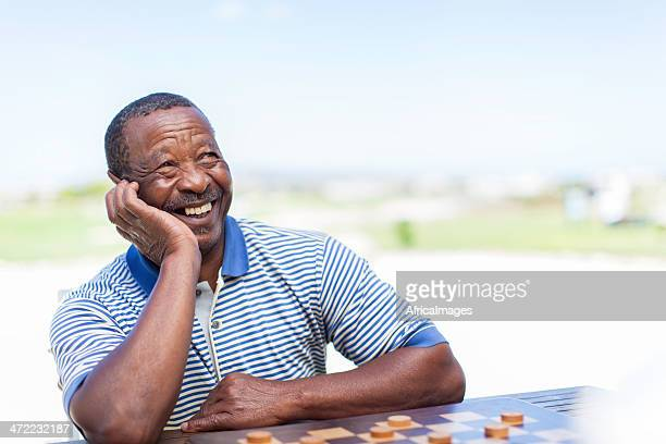 Happy african senior chess player