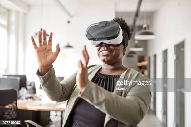 happy african using virtual reality glasses in office - virtual reality simulator stock pictures, royalty-free photos & images