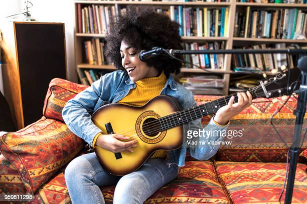 happy african woman singing and playing a guitar in studio - songwriter stock pictures, royalty-free photos & images