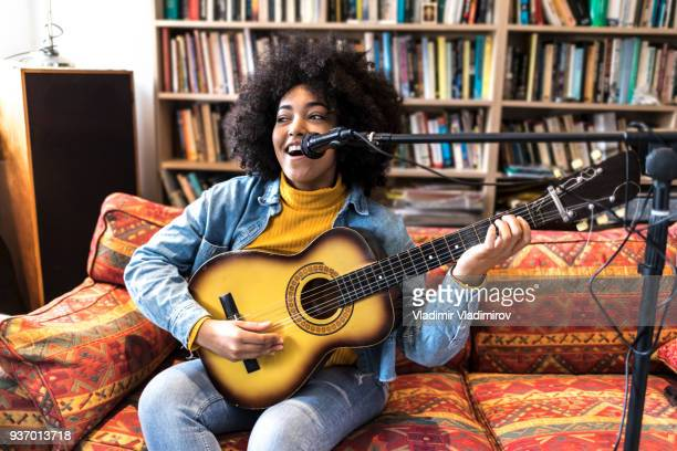 happy african woman singing and playing a guitar - acoustic music stock pictures, royalty-free photos & images