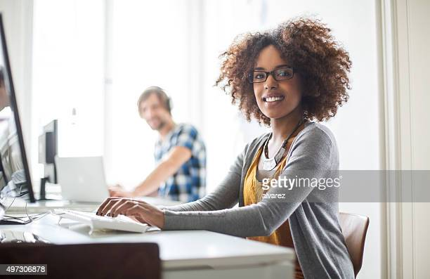 Happy african woman working at her desk