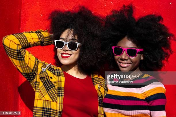 donne africane felici con occhiali da sole in piedi su sfondo rosso - afro foto e immagini stock