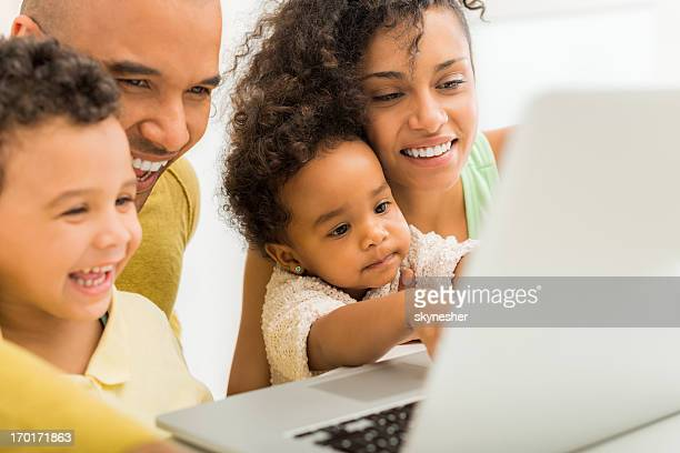 Happy African-American family using laptop