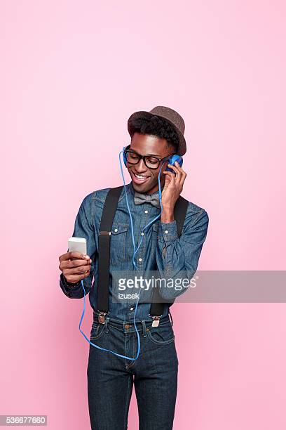 Happy afro american guy listen to music using smart phone