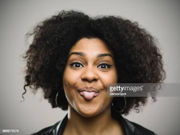 Heureuse femme américaine afro grimaçant sur fond gris