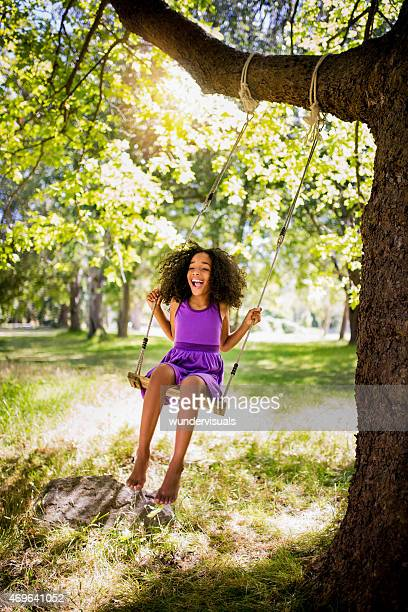 Happy Afro girl smiling and swinging in a park