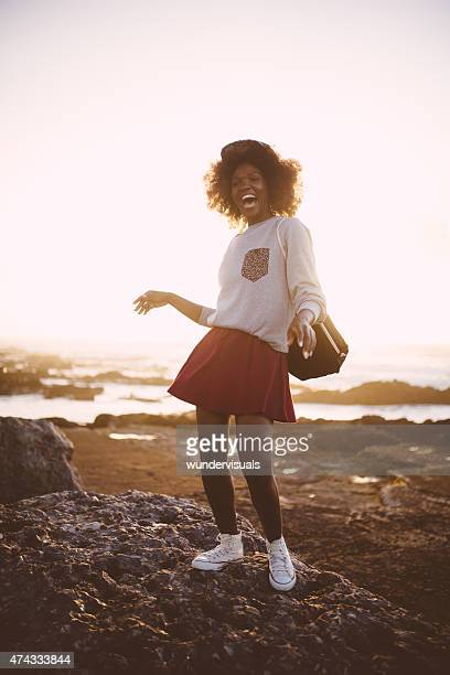 Happy Afro hipster teen girl posing joyfully at beach