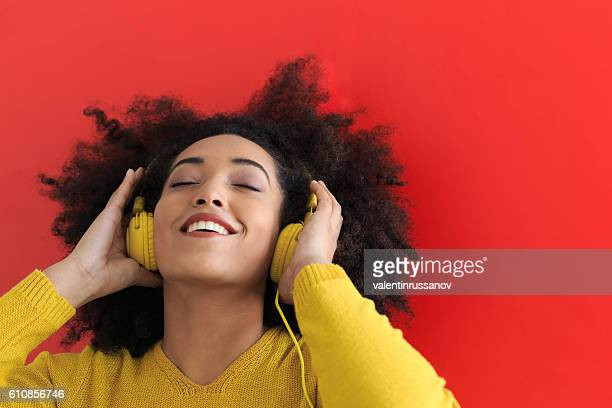 Happy afro woman listening music with yellow headphones