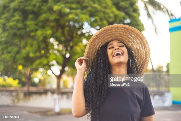 happy afro woman outdoors - green hat stock pictures, royalty-free photos & images
