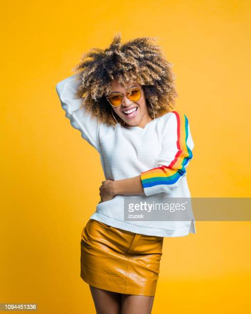 happy afro young woman dancing against yellow background - black skirt stock pictures, royalty-free photos & images