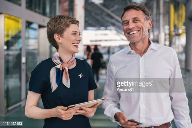 happy airline employee with tablet and passenger with cell phone at the airport - crew stock pictures, royalty-free photos & images