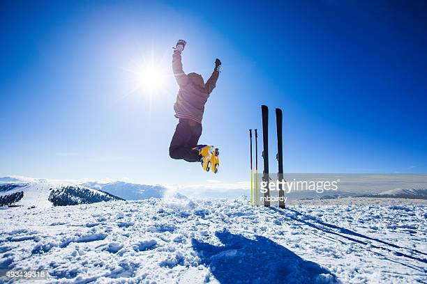 Happy alpine skier jumping in air on the top