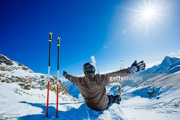 Happy alpine skier sitting on the edge