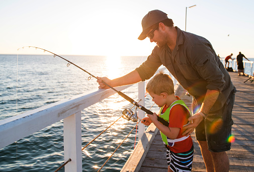happy American father teaching little young son to be a fisherman, fishing together on sea dock embankment enjoying and learning using the fish rod on a sunny Summer day 909847308