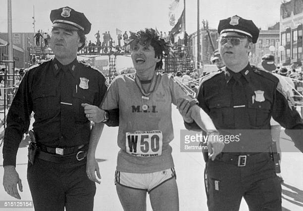 A happy American woman runner Rosie Ruiz of New York is supported by two Boston police officers as she makes her way to the dressing room after...