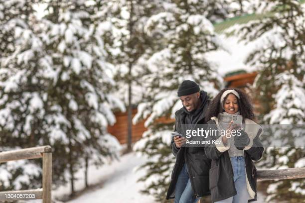 happy and attractive and stylish couple engage their smart phones outside in a winter setting - holiday stock pictures, royalty-free photos & images