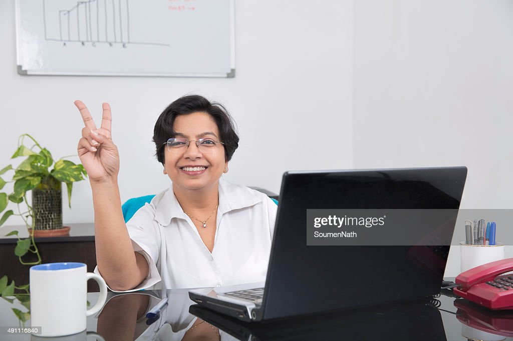 Happy and cheerful business woman showing Victory Sign : Stock Photo