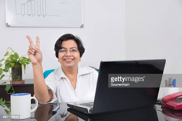 Happy and cheerful business woman showing Victory Sign