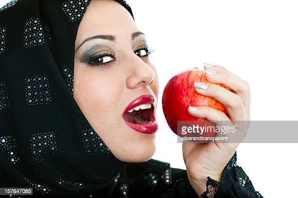 Happy and healthy Arabic girl eating an apple