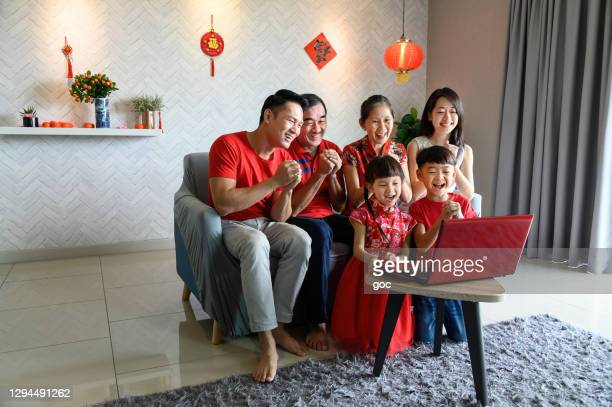 happy and joyful asian family having online chinese new year greeting and gathering with relatives using video call on laptop computer at home during pandemic. - chinese new year stock pictures, royalty-free photos & images