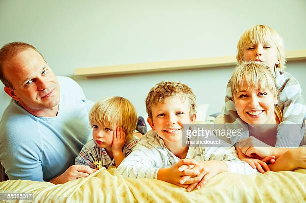 Happy and loving real family of five on a bed.