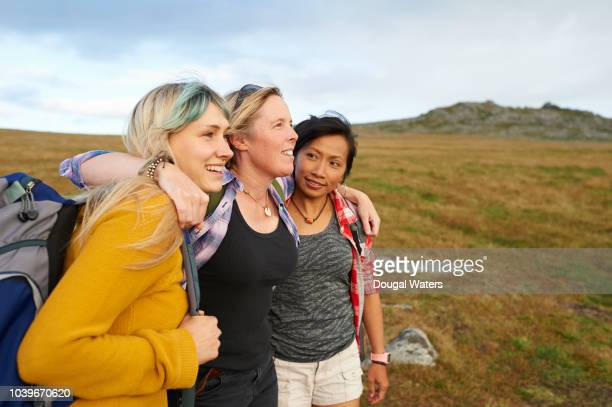 happy and positive hiking friends huddle together on a rocky moorland. - female friendship stock pictures, royalty-free photos & images