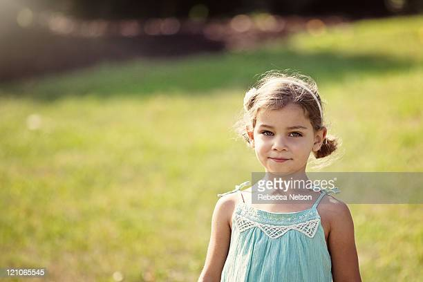 happy and pretty girl standing in grassy area - rebecca nelson stock pictures, royalty-free photos & images