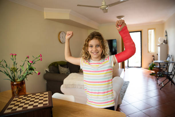 Happy and proud young girl with broken arm with cast