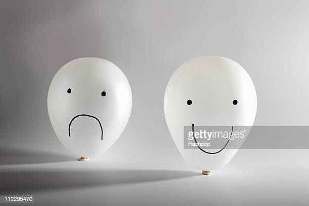 Happy and sad balloon faces