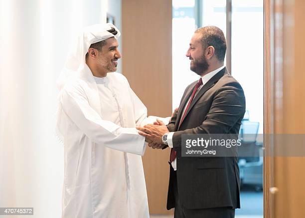 Happy Arab businessmen shaking hands in office