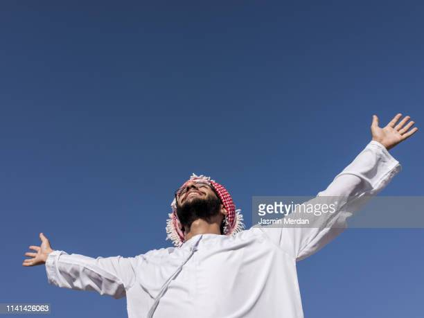 happy arab man with open arms and sky in background - jordanian workforce stock pictures, royalty-free photos & images