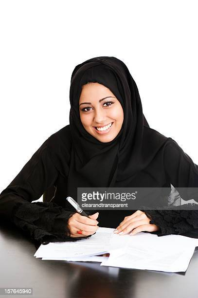Happy Arabic girl signing papers