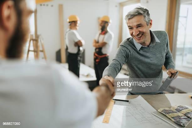 glücklich architekt gruß arbeiter auf der baustelle. - handwerker stock-fotos und bilder