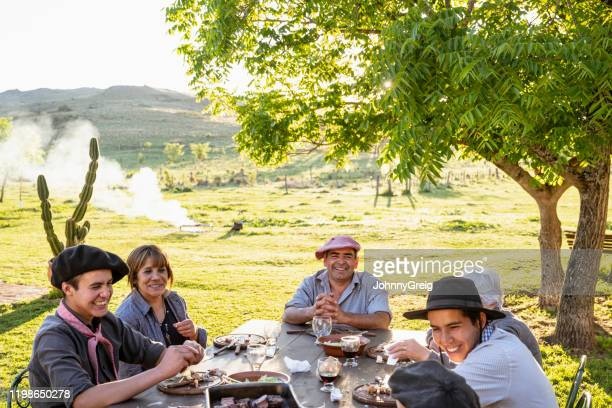 happy argentine gaucho family relaxing outdoors after meal - cultura argentina imagens e fotografias de stock