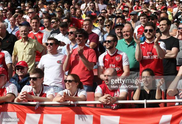 happy Arsenal supporters in the sunshine during the Premier League match between Arsenal and West Ham United at Emirates Stadium on April 22 2018 in...